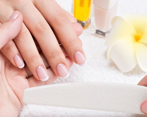 Woman in a nail salon receiving manicure by a beautician. Beauty treatment concept.